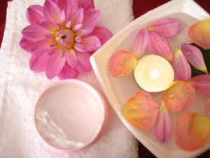 spa essentials (cream, towel and candle with flowers)